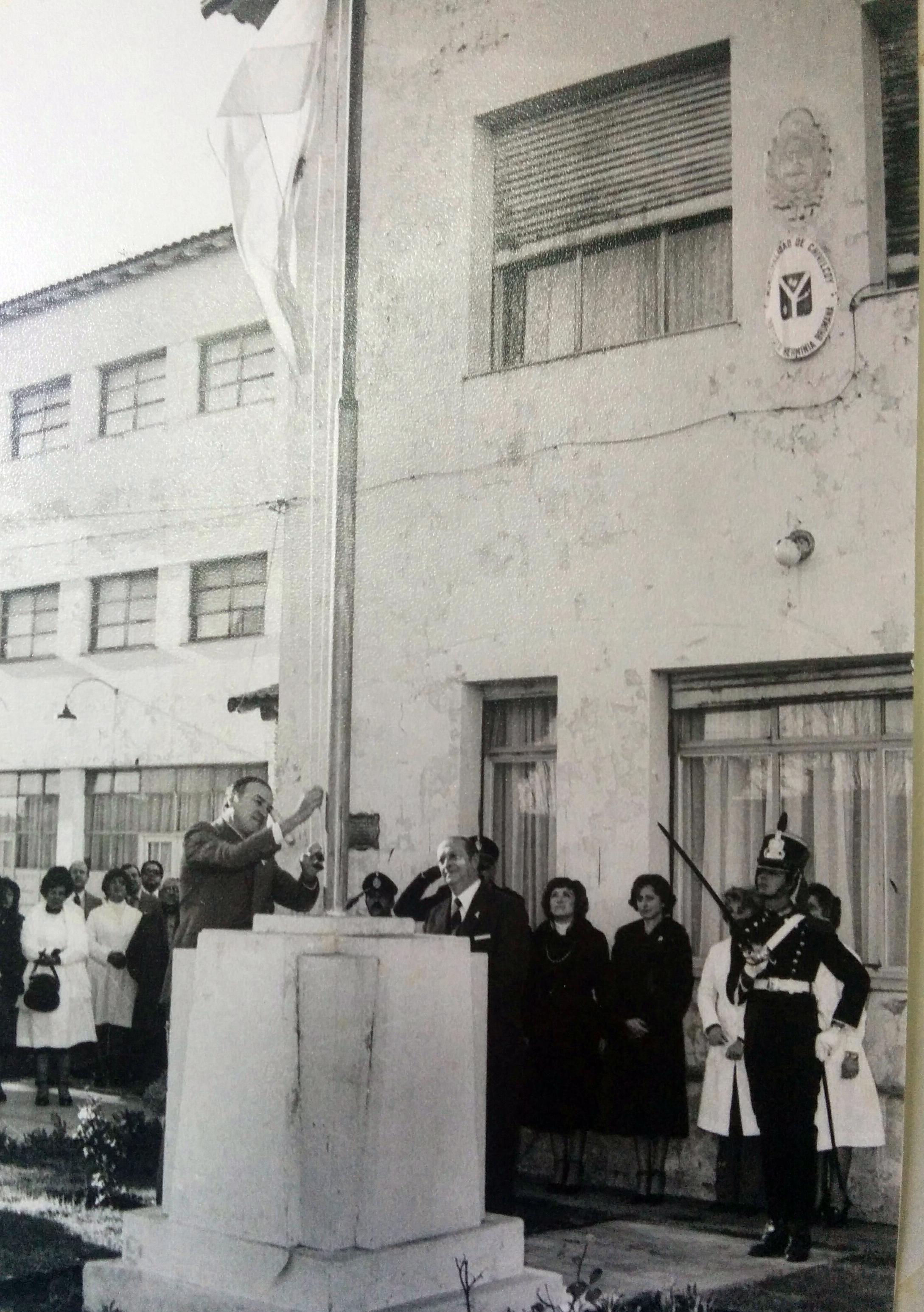 El secretario de Gobierno de la comuna, e intendente municipal interino, agrimensor Héctor Miguel Massino, al izar la bandera, en el mástil del Instituto Brumana, antes del comienzo de una ceremonia oficial. Año 1980.