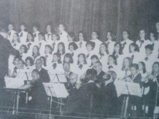 """El profesor Grisolía, a cargo de la dirección de la Orquesta de Cámara, de Chivilcoy, y el Coro de la Escuela Normal """"Domingo Faustino Sarmiento""""."""