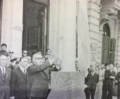 El entonces intendente muncipal, Edgar Ángel Frígoli, enarbolando la enseña patria, en el mástil del Palacio, durante los actos conmemorativos, del 119 aniversario, de la fundación de nuestra ciudad, el 22 de octubre de 1973.